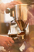 Close up barista using espresso machine grinder