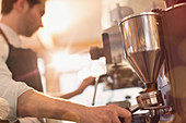Barista using espresso machine grinder