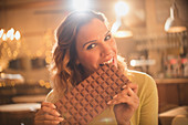 Woman biting into large chocolate bar