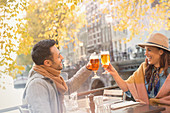 Young couple toasting beer glasses