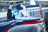 Formula one race car driver and cheering with fist