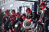 Pit crew ready with tires in formula one pit lane