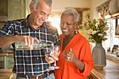 Senior couple pouring white wine in kitchen
