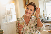 Mature woman drinking white wine in kitchen