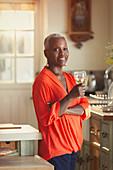 Portrait senior woman drinking wine in kitchen