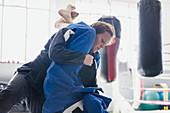 Determined woman practicing jiu-jitsu, tackling in gym