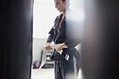 Young woman tying jiu-jitsu belt in gym