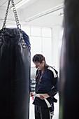 Young woman tying jiu-jitsu belt next to punching bag