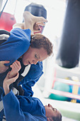 Determined women practicing jiu-jitsu in gym