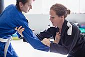 Focused women practicing jiu-jitsu in gym