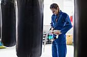 Young woman tying jiu-jitsu belt at punching bags