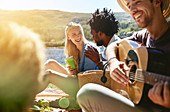 Young friends playing guitar and enjoying picnic