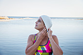 Female swimmer tucking hair into swimming cap