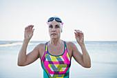 Portrait serious mature female swimmer at ocean
