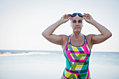 Mature female swimmer adjusting swimming goggles