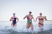 Female swimmers running and splashing