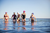 Female swimmers walking, wading