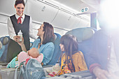 Smiling flight attendant bringing baby bottle