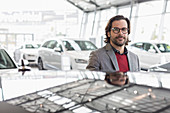 Portrait car salesman in showroom