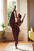 Graceful woman practicing yoga king dancer pose