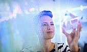 Female entrepreneur examining glass cube prototype