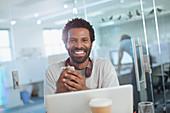 Portrait Businessman using smartphone at laptop