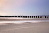 Tranquil pier over sandy estuary, UK