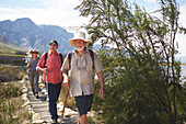 Active senior friends hiking along footpath