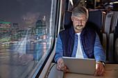 Man using digital tablet on train at night