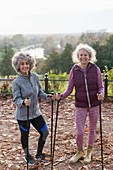 Portrait active senior women friends hiking with poles