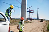 Engineers on dirt road at wind turbine power plant