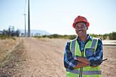 Portrait smiling engineer on dirt road
