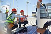 Female engineers talking, examining solar panels