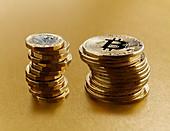 Golden Bitcoins stacked next to British pound coins