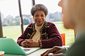 Portrait smiling senior businesswoman using laptop