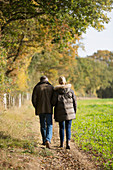 Mature couple walking in sunny, rural autumn field