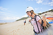 Smiling female paraglider with equipment on beach