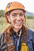 Portrait smiling, muddy woman zip lining
