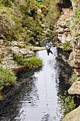 Woman zip lining over stream