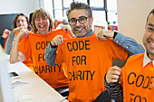 Portrait hackers in t-shirts coding at hackathon