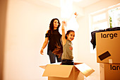 Playful mother and daughter moving into new home