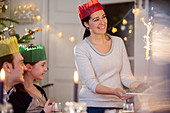 Mother in paper crown serving Christmas pudding