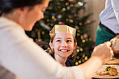 Smiling girl in paper crown at Christmas dinner