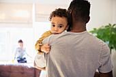 Portrait innocent baby boy over fathers shoulder