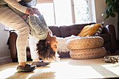 Mother holding daughter upside-down in living room