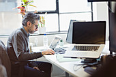 Focused businessman working at laptop in office