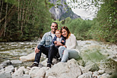 Parents and baby son sitting on rocks at riverside