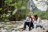 Parents and baby son sitting on rocks along stream