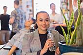 Portrait businesswoman drinking bottled water