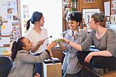 Creative female designers toasting green smoothies